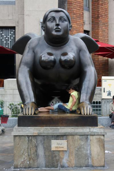 Girl resting against a leg of the Sphinx | Plaza Botero | Colombia