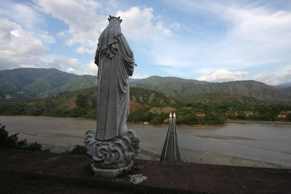 Statue, bridge over the Cauca River, and the rolling landscape | Puente de Occidente | Colombia