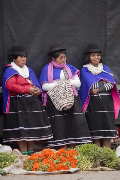 Three Guambiano women in traditional dress and bowler hat with their vegetables | Silvia Market | Colombia