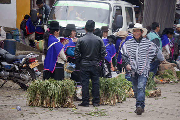 Man in poncho and with a big smile walking past a row of Guambiano market women - 哥伦比亚