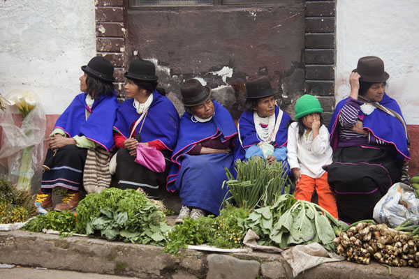 Picture of Row of Guambiano market women sitting on the sidewalk, selling their vegetables
