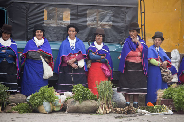 Foto de Bowler hat, blue dress: Guambiano women in their traditional attire selling vegetables at the market of Silvia - Colombia - América