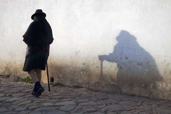 Foto van Woman walking past a white wall in Villa de LeyvaVilla de Leyva - Colombia
