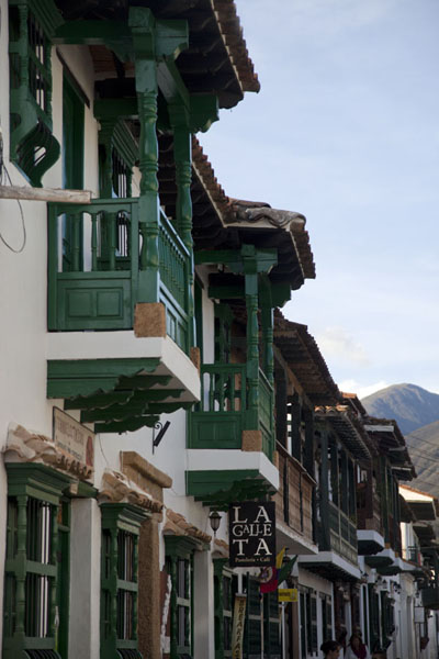 Foto van White houses with green balconies and window shutters in a street of Villa de LeyvaVilla de Leyva - Colombia