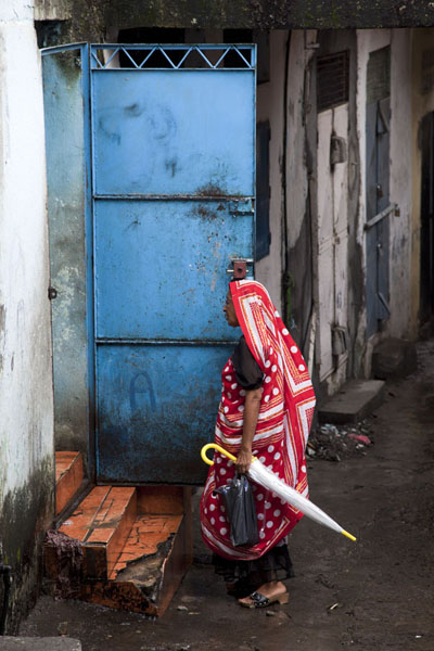 Picture of Mutsamudu medina (Comoros): Anjouan woman with traditional cloth at a door in the medina of Mutsamudu