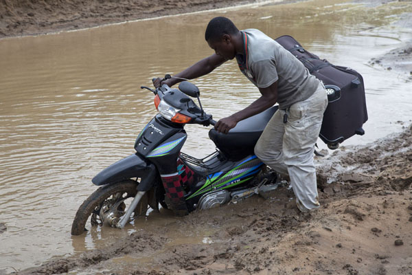 One of the motor guys trying to get the bike through a muddy pool | Cruce de frontera de Vaga | República del Congo