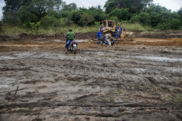 Getting the motorbikes to the other side of the muddy track | Cruce de frontera de Vaga | República del Congo