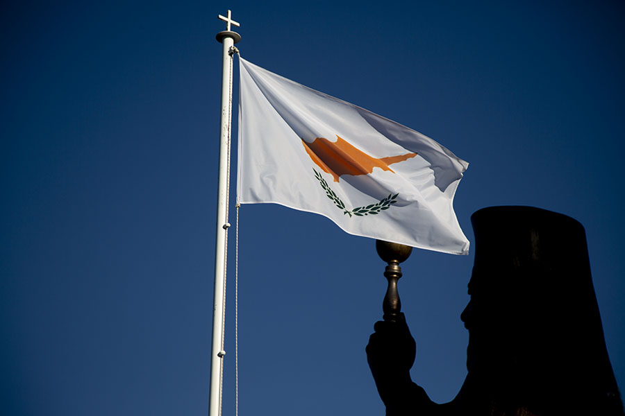 Foto di Silhouette of former president of Cyprus Makarios III with the flag of CyprusThroni - Cipro