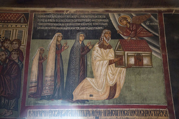 Foto van Priest Chamados, with his wife and daughters, offering a model of the church to Christ in Archangel Michael church in PedoulasTroodos - Cyprus