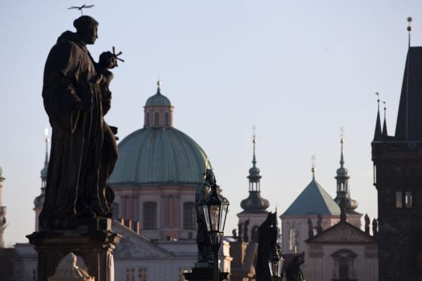 Statue of St. Anthony of Padua and other statues and lanterns on Charles Bridge with the cupola of St. Francis of Assisi church | Charles Bridge | Czech Republic