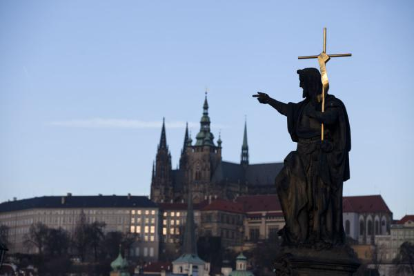 Statue of St. John the Baptist with cross on Charles Bridge with Prague Castle in the background | Praga | Repubblica Ceca