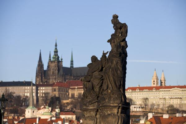 Statue of Madonna with St. Thomas Aquinas and St. Dominique on Charles Bridge with Prague Castle in the background | Praga | Repubblica Ceca
