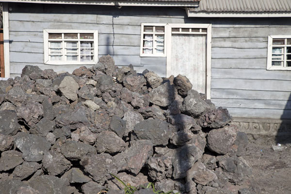 Wooden house in Goma with pile of volcanic rocks in front of it | Goma | Rep. Democratica del Congo