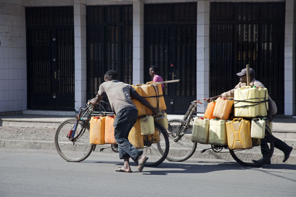 Young men walking bikes loaded with jerrycans full of water | Goma | Rep. Democratica del Congo