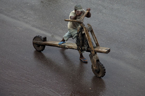 Tshukudu driver pushing his traditional vehicle up the main boulevard of Goma | Goma | Democratic Republic Congo