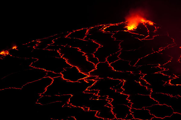 Bright orange lines contrasting with black areas in the lava lake of Nyiragongo | Nyiragongo Vulkaan | Democratische Republiek Congo