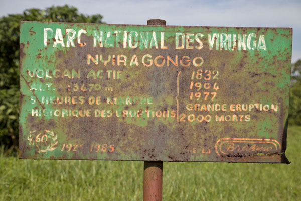 Foto van The deathly influence of Nyiragongo explained on a rusty sign at its foot - Democratische Republiek Congo - Afrika