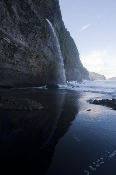 Picture of Ravine Cyrique waterfall (Dominica): Ravine Cyrique reflected in the water and black sand with wild waves in the background