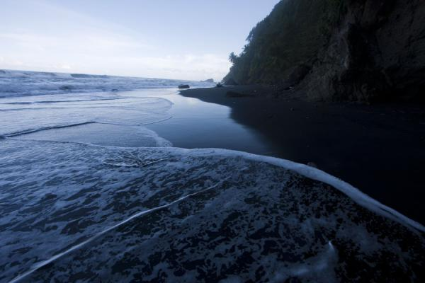 Foto van Waves washing over the black sand of the beach of the Ravine Cyrique waterfallRavine Cyrique waterval - Dominica