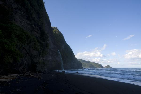 Foto van The black sand beach and waterfall at the foot of the cliffsRavine Cyrique waterval - Dominica