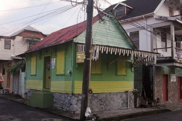Foto de Wooden house on a corner painted green and yellowRoseau - Dominica