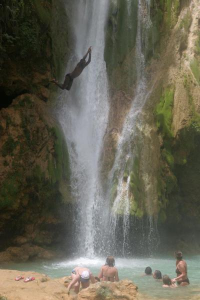 Photo de Jumping from the waterfall: guy coming down while tourists look in aweCascades Limón - République dominicaine
