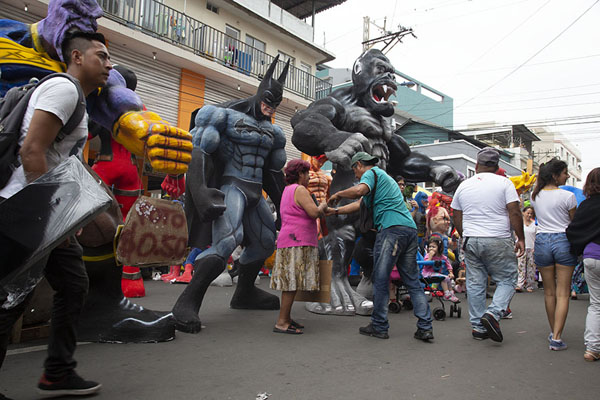 People walking past enormous paper-maché dolls | Año viejo effigy dolls | Ecuador