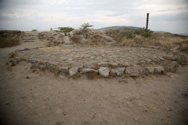 Photo de l'Equateur (View of lithic disk with pillar and monument marking the equator in the background)