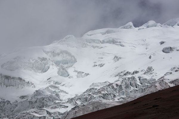 Foto van Clouds swirling over the glacier covering the summit of CotopaxiCotopaxi - Ecuador