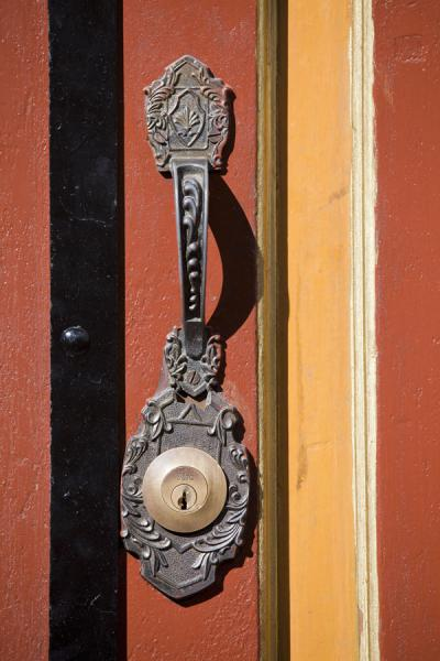 Picture of Detail of orange and yellow wooden door and lock in Cuenca