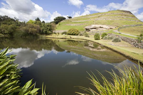 Foto di Small pool reflecting the ruins of the Tomebamba Inca ruins on a hill - Ecuador - America