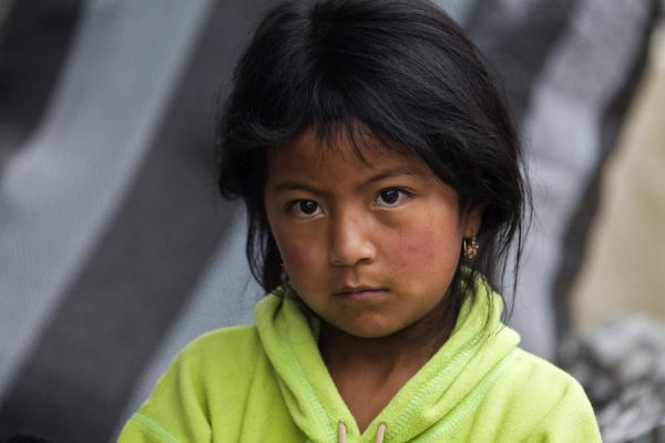 Picture of Otavalo market women (Ecuador): Sweet and serious stare of girl at the market of Otavalo