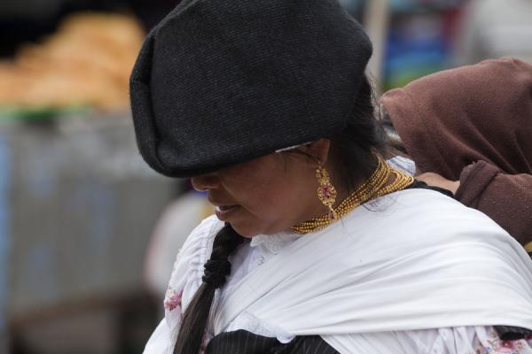 Picture of Otavalo market women (Ecuador): Woman at the market of Otavalo with child on her back