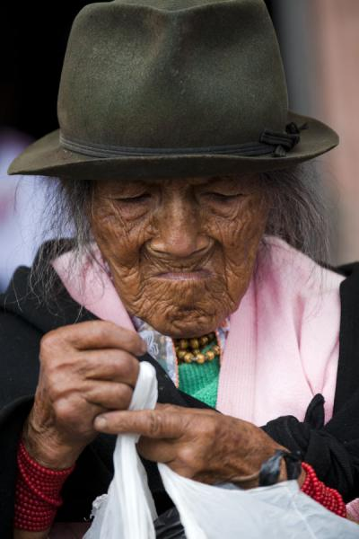 Old woman with hat getting her things ready | Otavalo market women | Ecuador