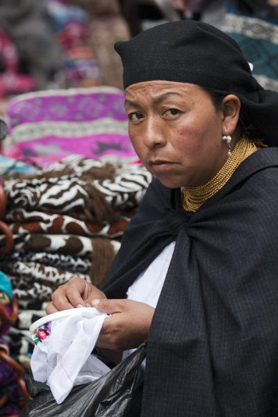 Picture of Otavalo market women (Ecuador): Otavalo market woman sewing at her stall