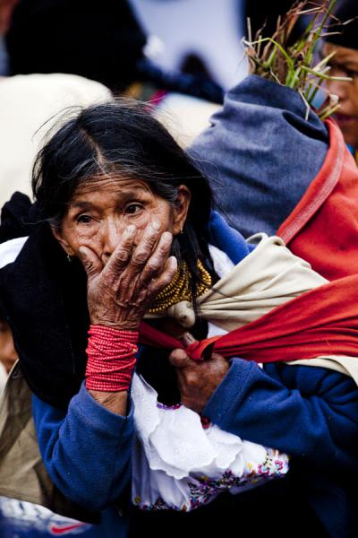 Picture of Otavalo market women (Ecuador): Old woman at Otavalo market carrying a load on her back