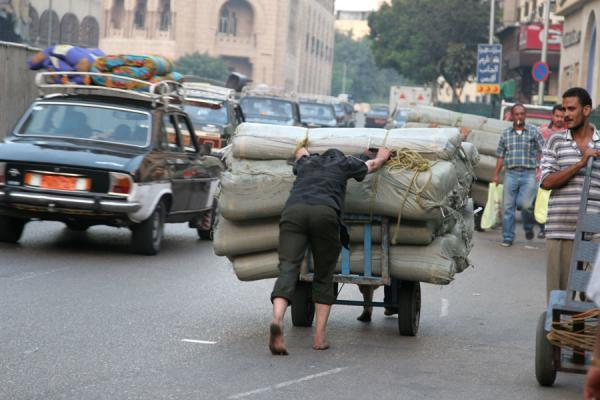 Man pushing a cart on a road | Darb al-Ahmar street scenes | Egypt
