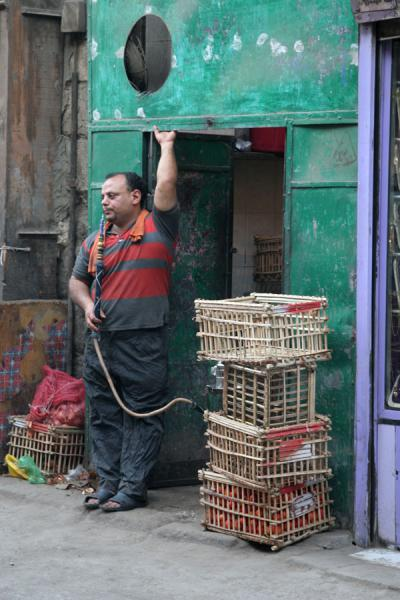 Smoking a shisha in front of his shop | Darb al-Ahmar street scenes | Egypt
