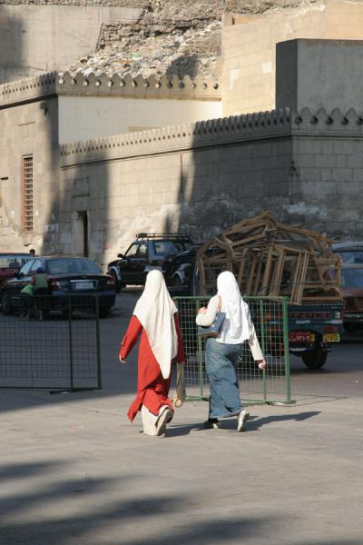Women with headscarfs walking in a street | Darb al-Ahmar street scenes | Egypt