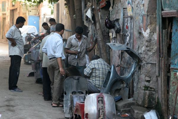 Picture of Darb al-Ahmar street scenes (Egypt): Egyptian men working in a scooter repair shop