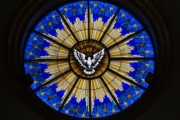 Photo de Sun shining through the stained glass window with the sacred dove above the entrance of the cathedral - El Salvador - Amérique