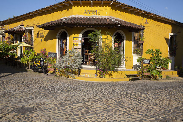 Yellow house with flowers on the corner of two cobble-stone streets | Suchitoto | 萨尔瓦多