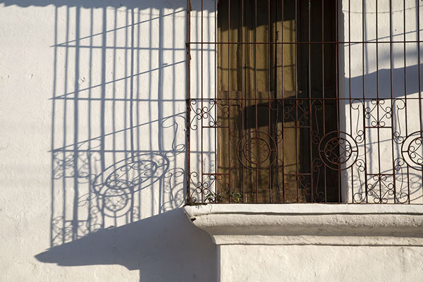 Sun casting a shadow of a metal bars protecting a window | Suchitoto | 萨尔瓦多