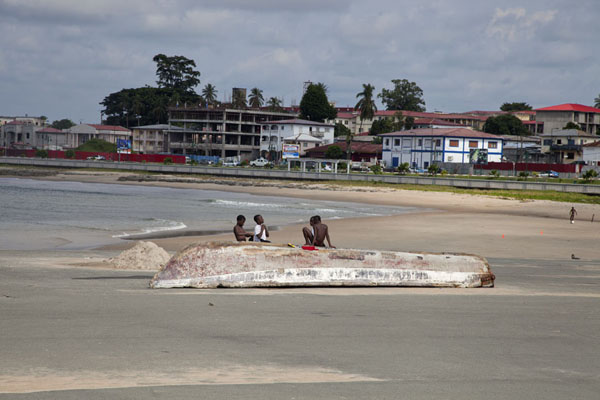 Kids playing on a boat just off the northern end of the waterfront of Bata | Bata waterfront | Equatorial Guinea