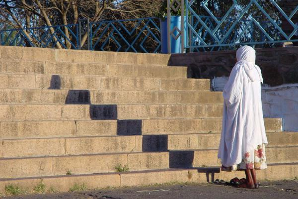 Woman standing in front of a church in Asmara | Eritrean people | Eritrea