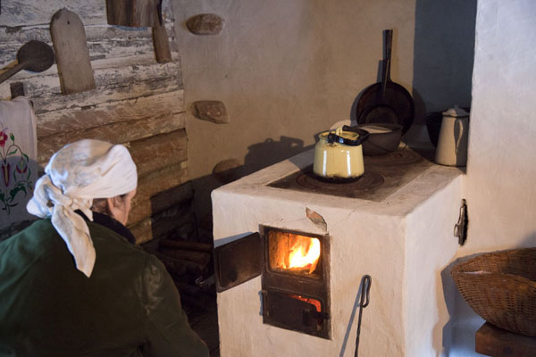 Estonian woman in traditional clothes checking the fire in her kitchen | Ests Openlucht Museum | Estland
