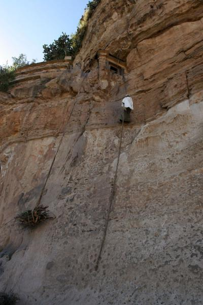 Picture of Debre Damo Monastery (Ethiopia): Priest climbing the wall to reach Debre Damo with a leather rope