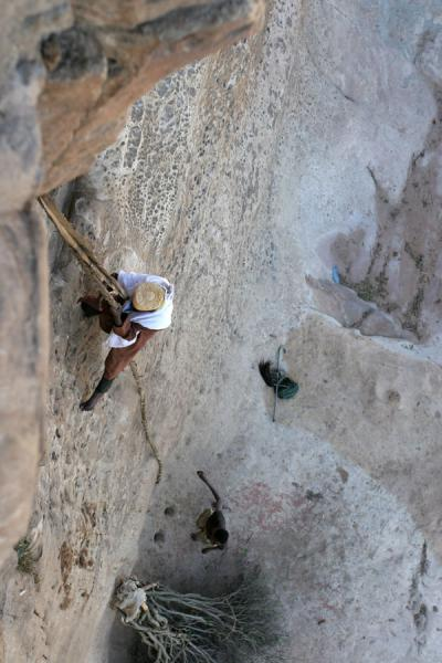 Old priest scrambling up the wall of Debre Damo | Debre Damo Monastery | Ethiopia