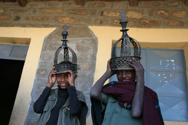 Two youngsters working at the church, posing with ancient crowns | Jóvenes etiopianos | Etiopia