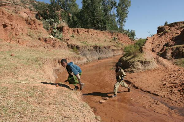Foto di Boys jumping over a creek near Debre Tsion churchGiovani etiopiani - Etiopia
